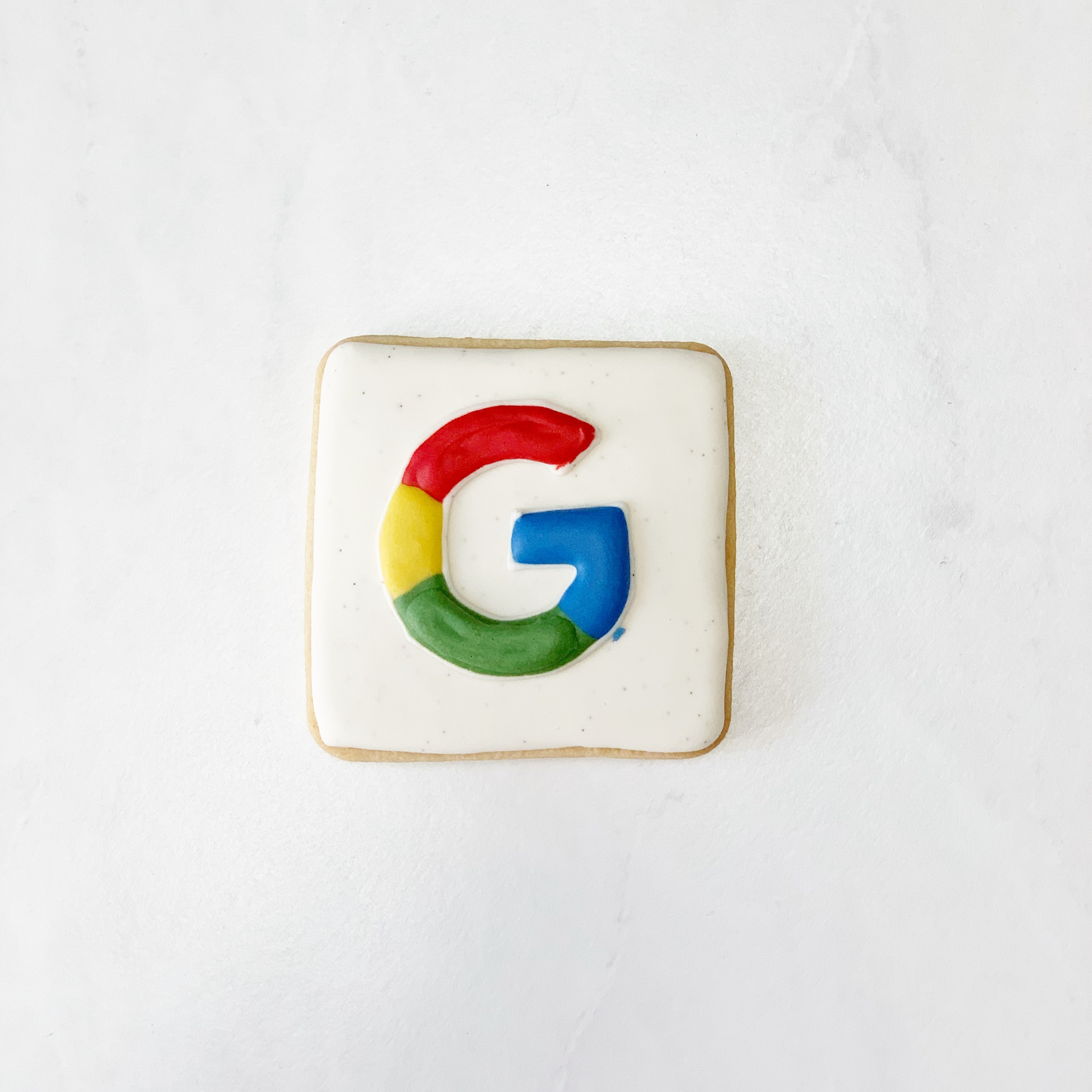 The Google logo on a square, white cookie.