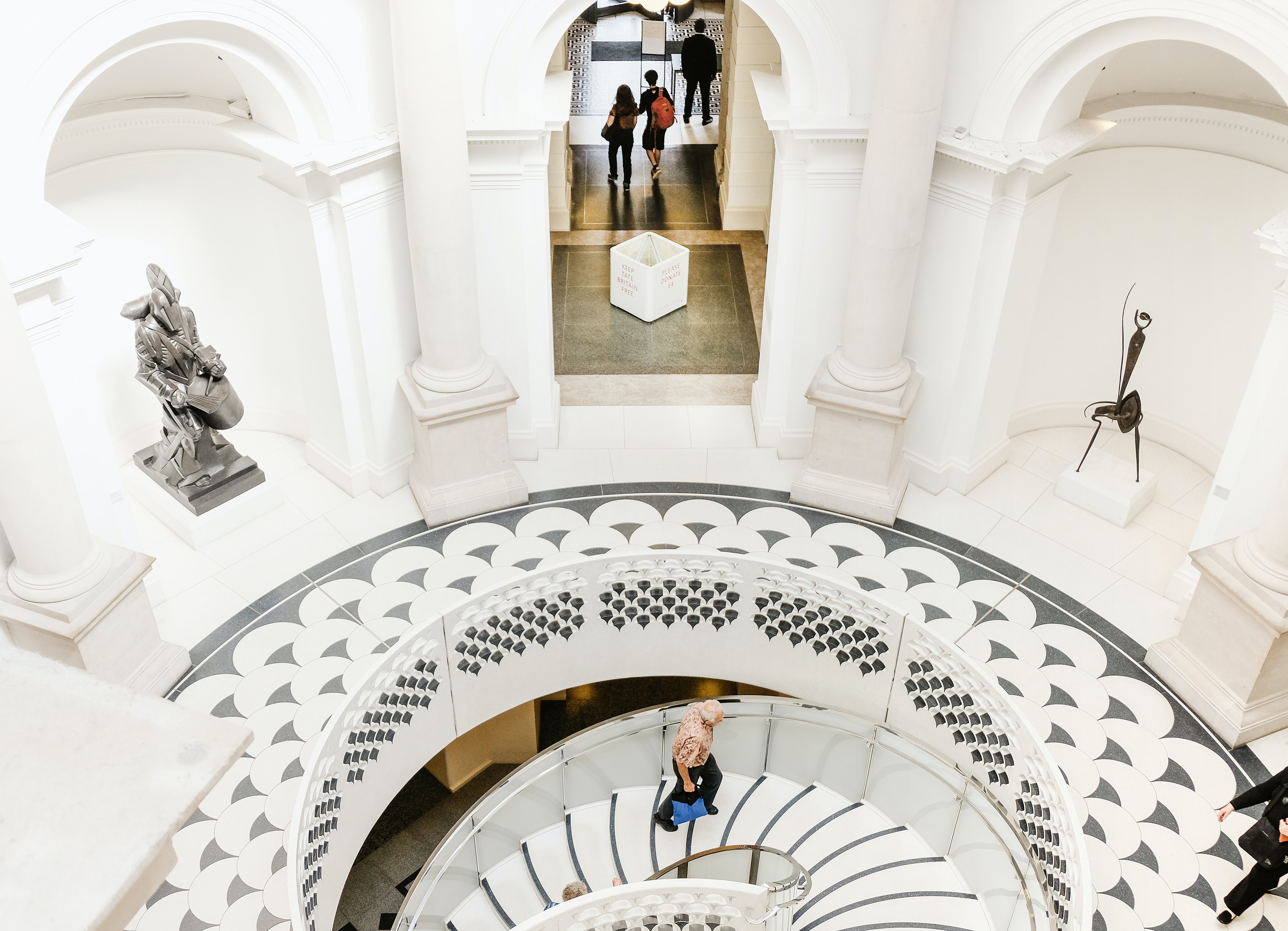 A circular staircase in the Tate Britain, primarily in white, is show from a bird's eye view. Patrons walk about looking at the art pieces.