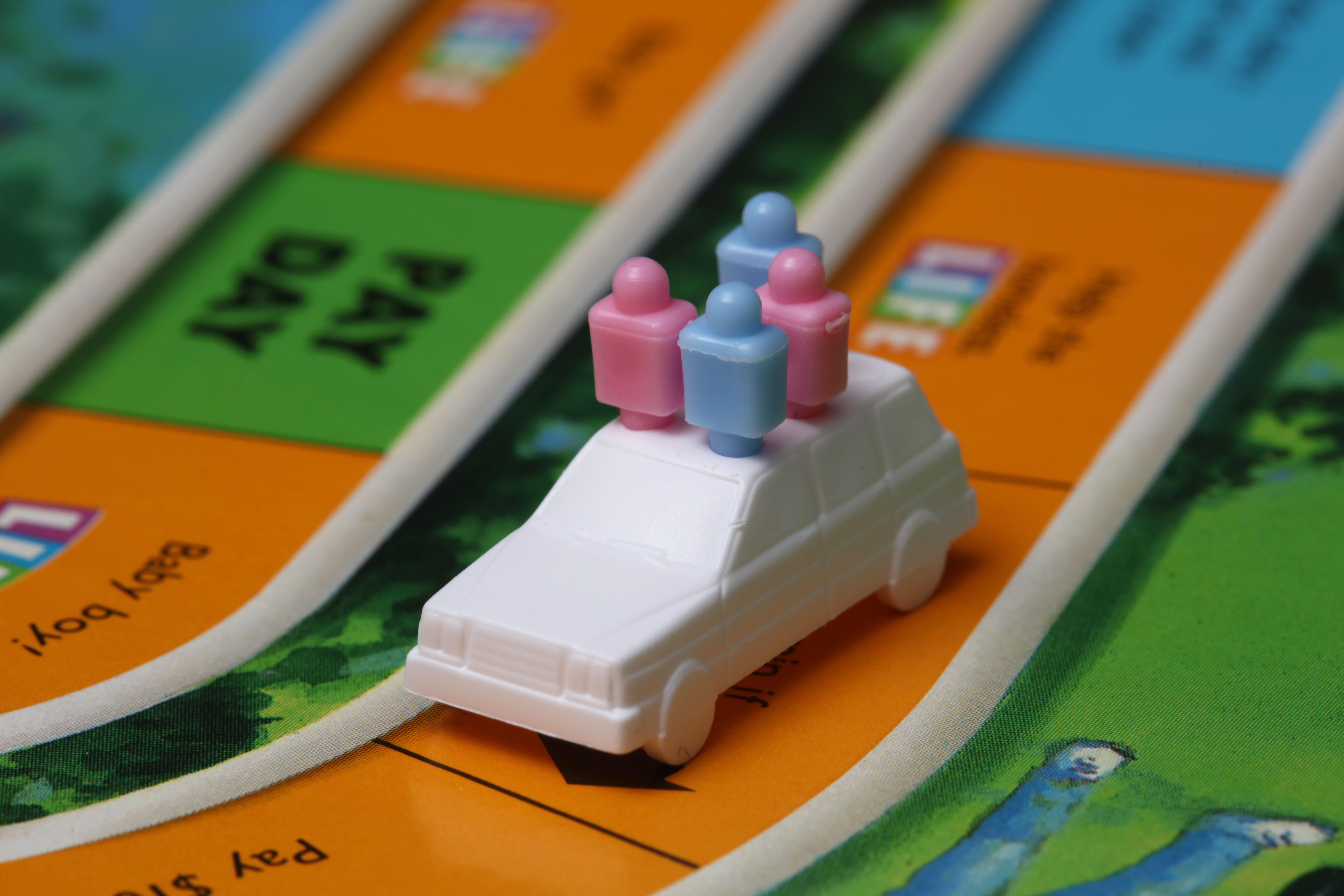A car game piece on a game board carrying two pink people and two blue people.