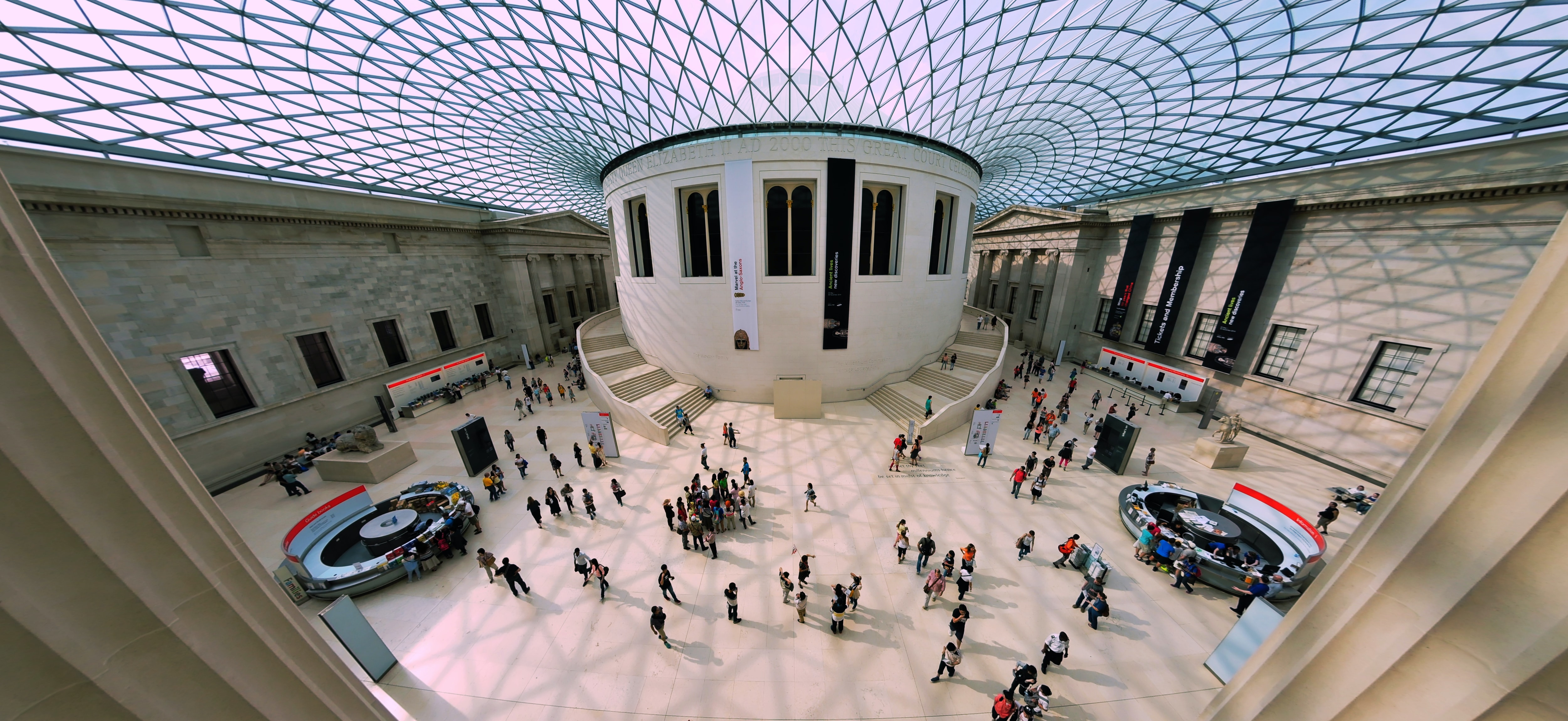 An aerial view of the inside of the British Museum with a glass roof, information desks, and people milling about.