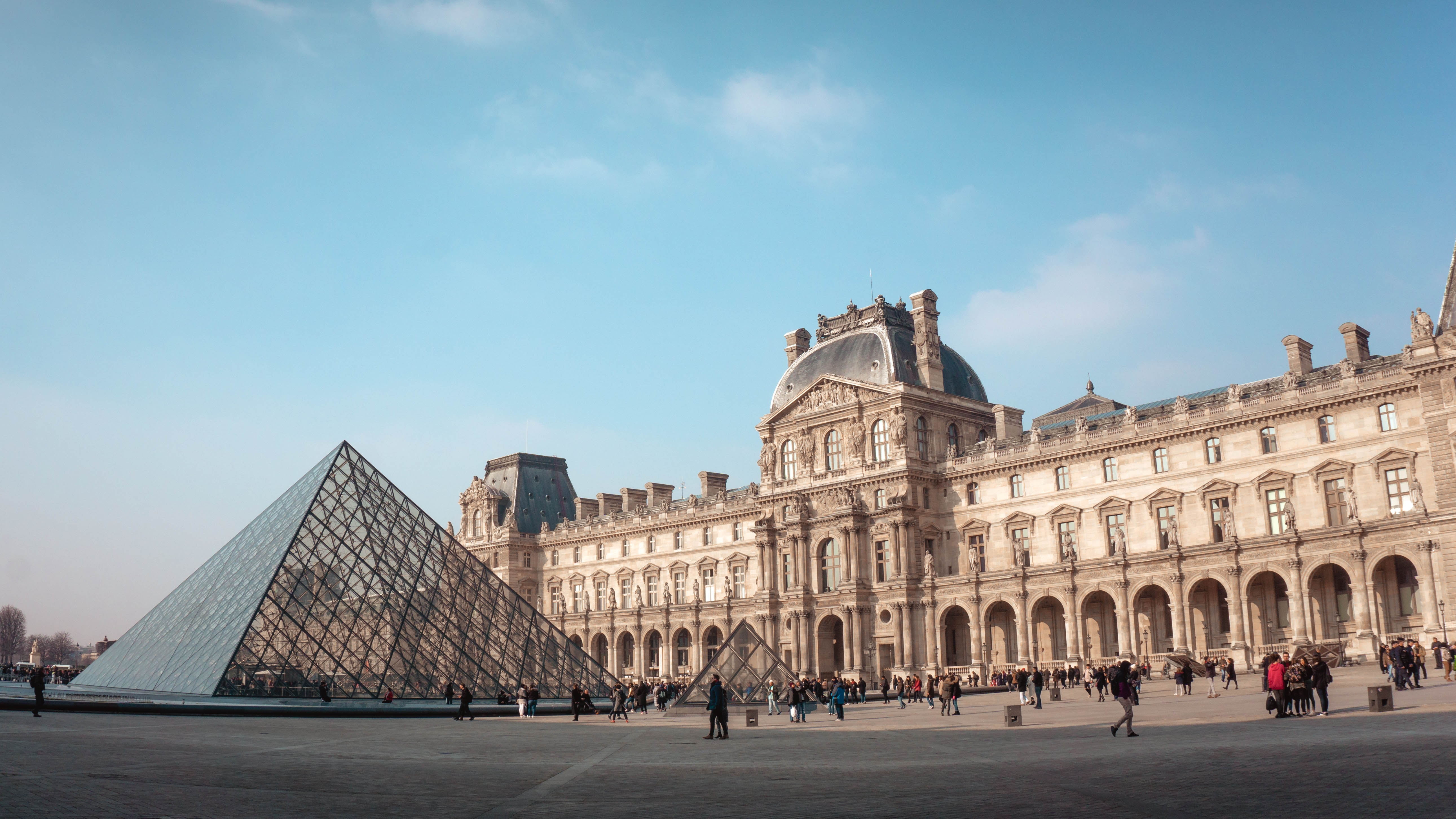 The image is of the Louvre museum with the iconic glass pyramid in front.