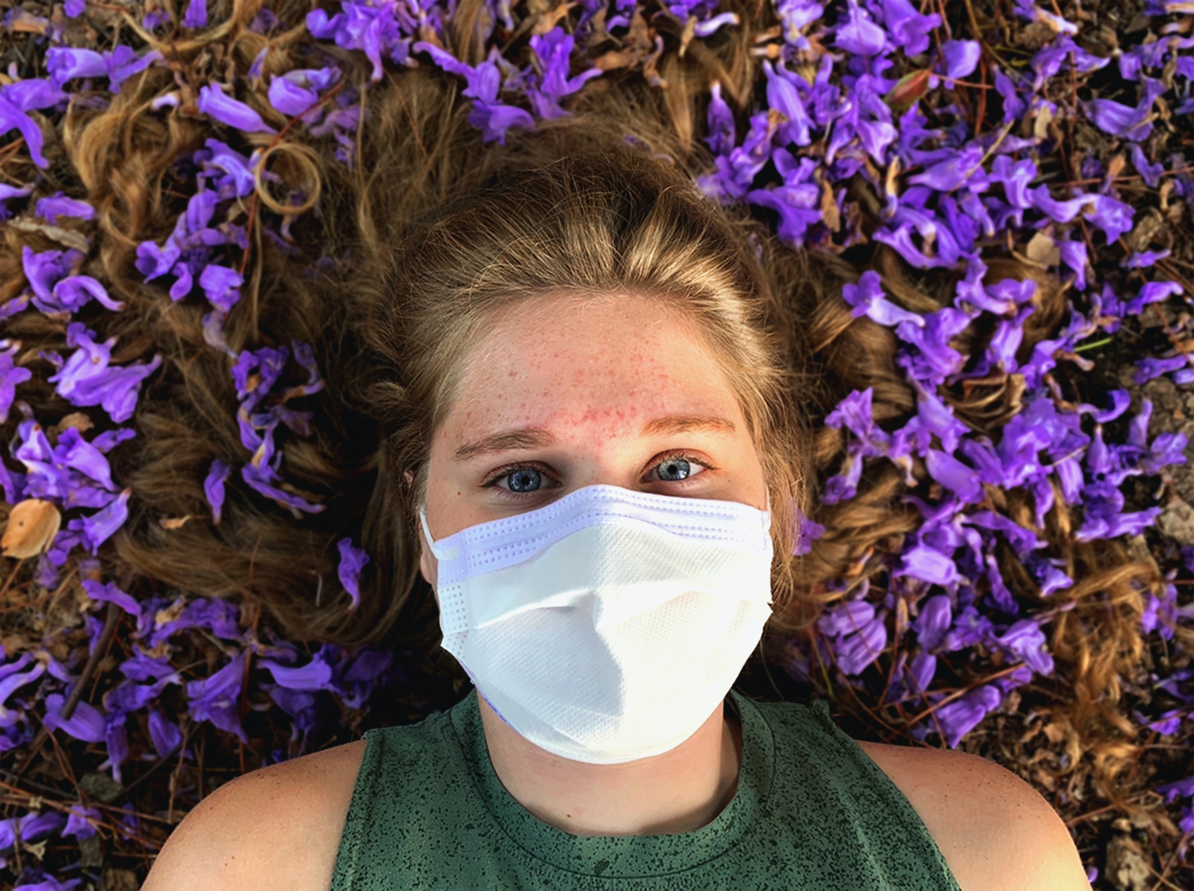 A young woman lays in a bed of purple flowers with her hair splayed out around her head. She is wearing a green top and a white mask.