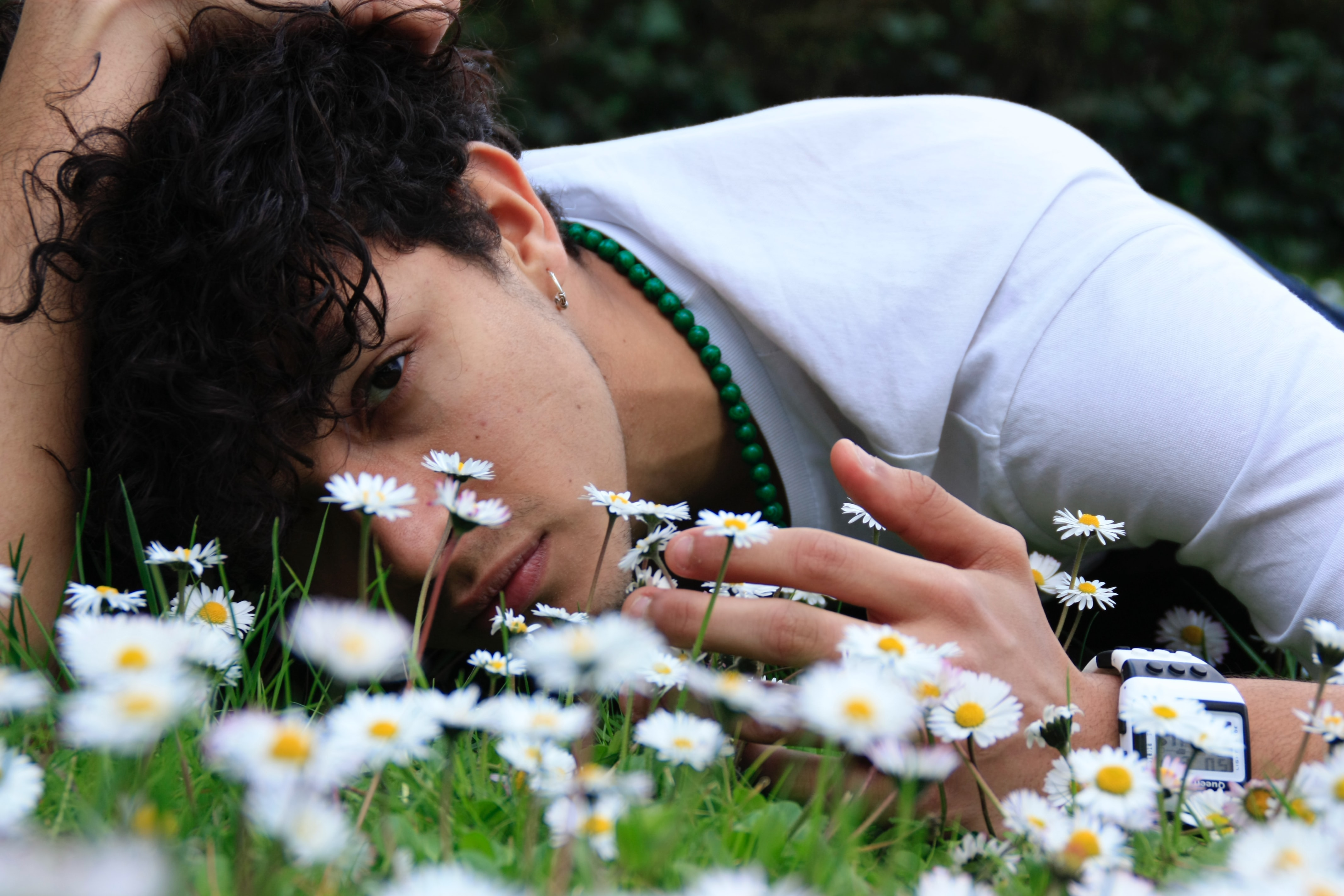 A young man is laying in the grass wearing a white shirt. There are small white flowers in front of his face.