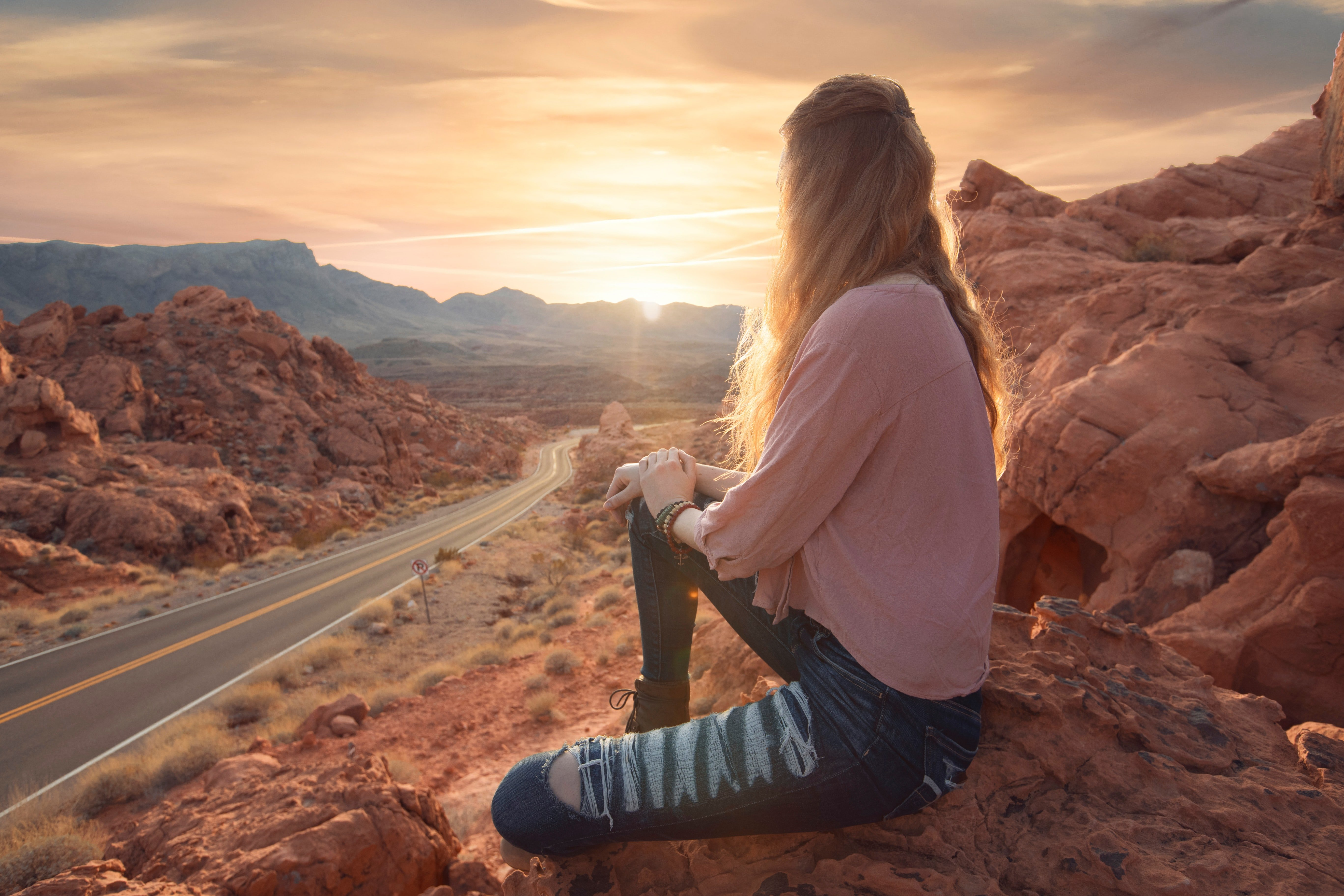 A young woman sits on a rocky mountainside staring down a long stretch of road into the sunrise.