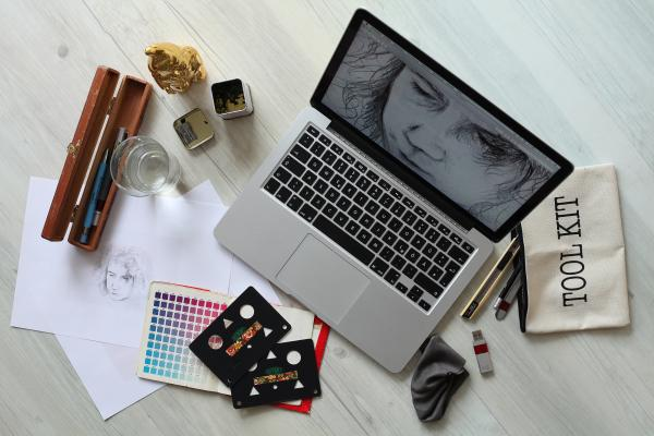 "On a tabletop, a laptop is open with the screen showing a drawn face, likely male. Around the laptop are an array of drawing tools, including a cream-colored canvas pencil bag that says ""TOOL KIT,"" a USB drive, a page of color swatches, tracing sheets for shapes, a few white pages of paper with the same sketched face that's on the laptop screen, a wooden case for drawing pens and pencils, a pencil sharpener, and a glass of water."