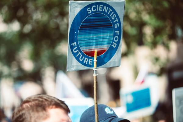 "IMAGE: People at a rally with a sign held up overhead saying ""Scientist for Future."""