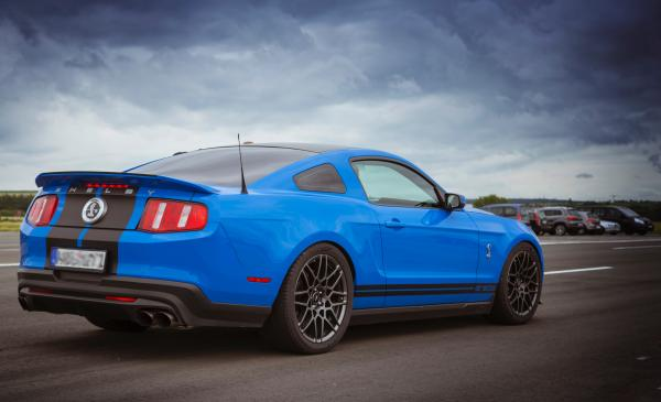 A picture of a blue Ford Shelby on the road with a dark sky.