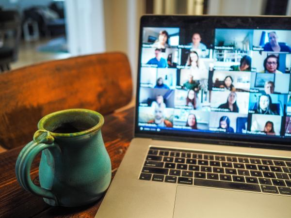 Image is of a computer with a video chat program up featuring dozens of faces. The computer is on a wooden table next to a blue ceramic mug.