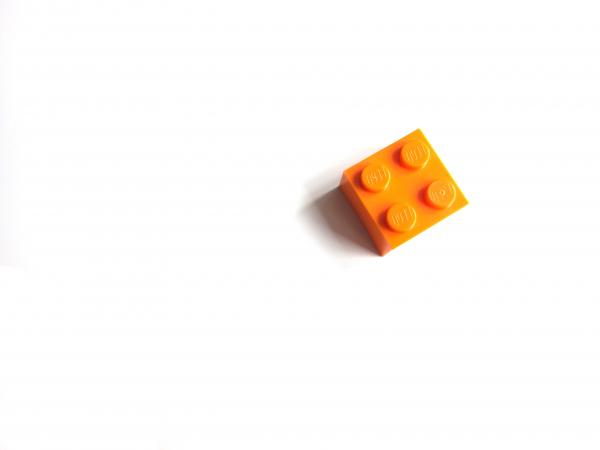 The image is of a single orange lego in the upper right-hand side of a white background.