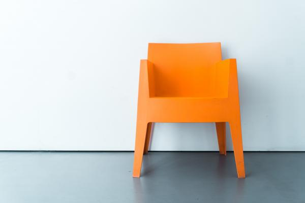 The image is of a bright orange chair in front of an off-white wall on a slate grey floor.