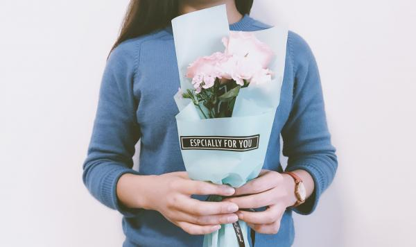 "A young woman in a soft blue shirt holds pink flowers in light blue wrapping with words on the front that say ""ESPECIALLY FOR YOU."""
